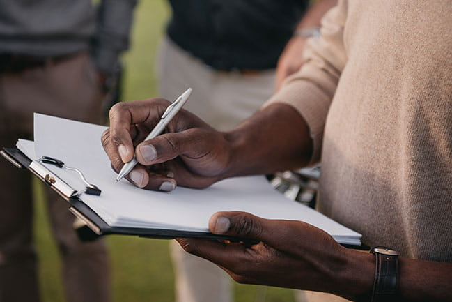 African-American man signing contract on clipboard