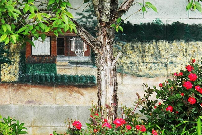 Photograph of flowers and mural on side of building
