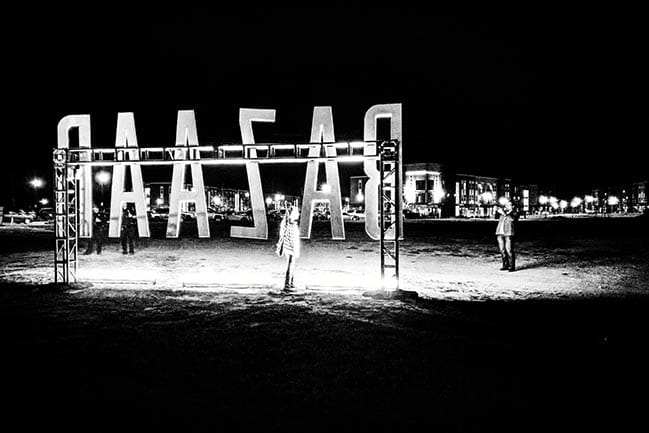 "Black and white photograph of giant letters spelling ""BAZAAR"" from behind"