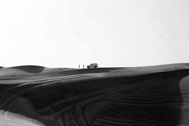 Black and white photograph of sand dunes in Dubai, with two people and an SUV in the distance