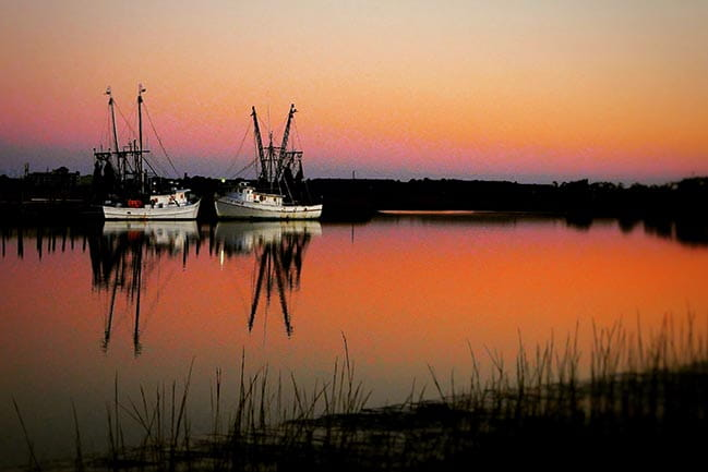 Color photograph of shrimping boats at dusk