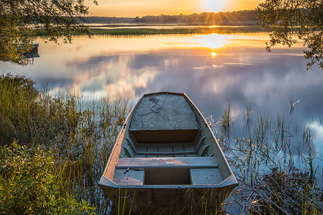 Color photograph of empty boat on creek at sunrise
