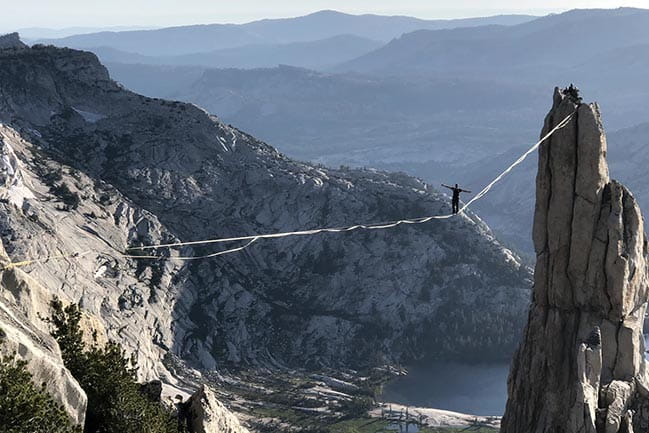 Color photograph of a man tightrope walking across two peaks in Yosemite