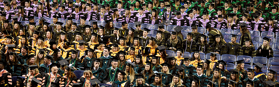 Graudates at a commencement ceremony sitting in their colorful regalia.