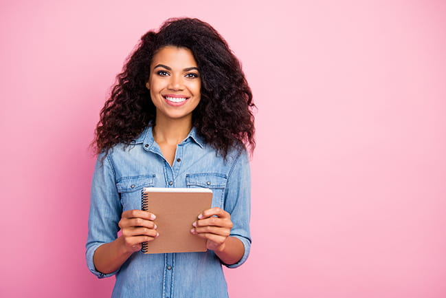Portrait of positive cheerful african american girl holding a notebook in front of pink background