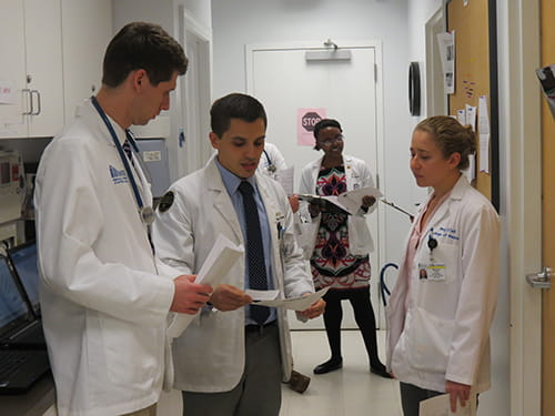 Three medical students look at notes and talk in a hallway