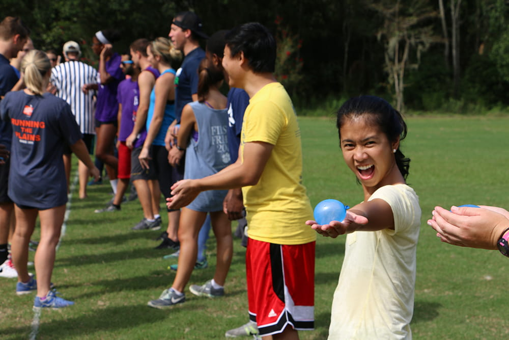 A young woman shows off a water balloon at a field day event