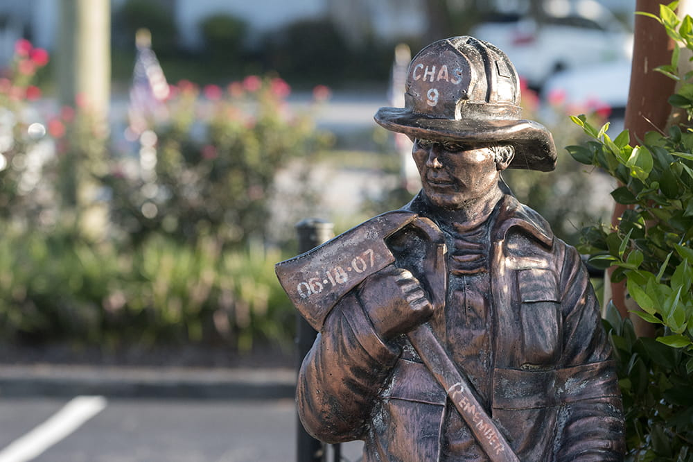 statue of a firefighter holding an ax with the date of 6-18-07, the words Chas 9 and Remember