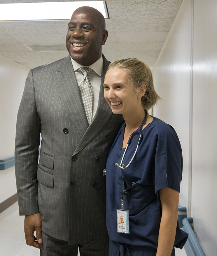 An MUSC physician poses for a photo with Magic Johnson