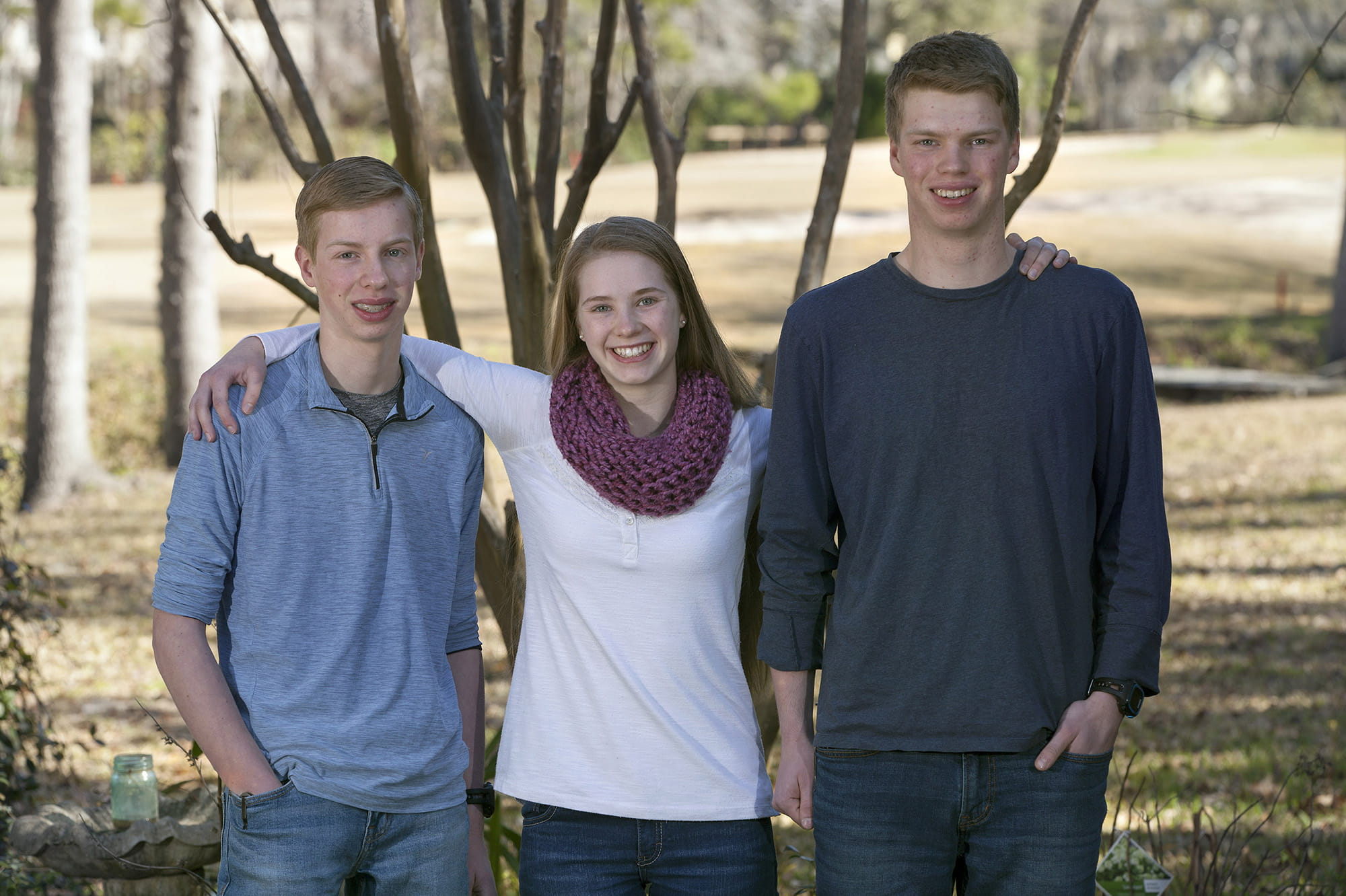16-year-old triplets stand for photo in their back yard