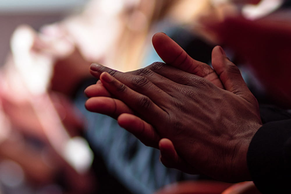 closeup of African American's hands clapping in crowd of people